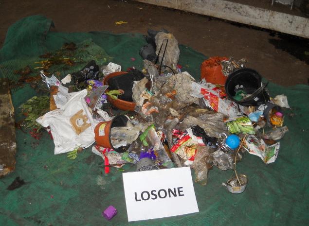 I rifiuti illegali, plastica, carta e altro, depositati impropriamente nel bidone del verde.